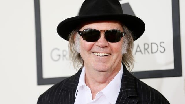 Neil Young im Nadelstreifenanzug mit Hut und Sonnenbrille.