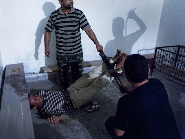 Syrische Oppositionskämpfer foltern einen Informanten mit einer Fussfessel.
