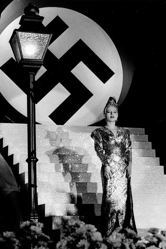 Sängerin vor Show Bühne. Im Hintergrund ein Hakenkreuz.