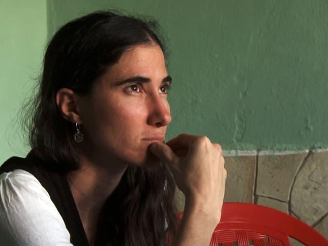 Die kubanische Bloggerin Yoani Sanchez sitzt an einem Tisch und sieht nachdenklich aus.