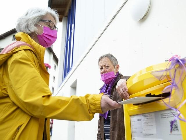 Frauen werfen das Stimmcouvert in einen gelben Postkasten.