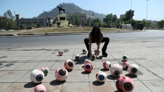 Plastikaugäpfel auf dem Boden. Ein Frau steht dahinter. Sie hat sie ausgelegt.