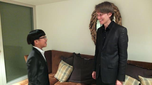 Yves Man, schwares Haar, Brille, Anzug steht vis-à-vis des Pianisten, der etwa zwei Köpfe grösser ist.