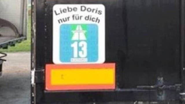 Eine grosse Autobahnvignette klebt am Heck eines Lastwagens mit der Aufschrift «Liebe Doris nur für dich».