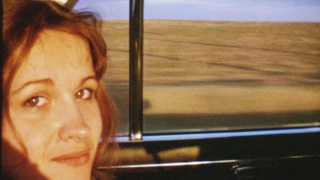 Eine junge Frau sitzt in einem Zug.