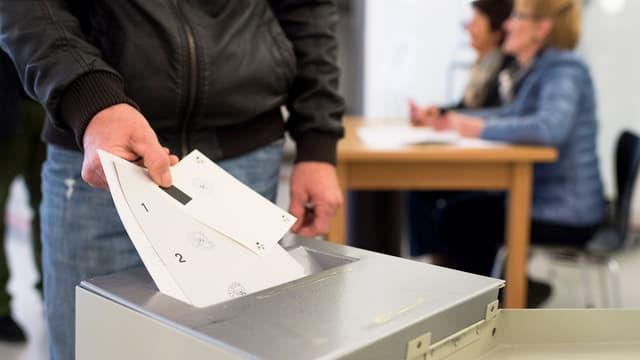 Ein Mann wirft seine Abstimmungszettel ein.