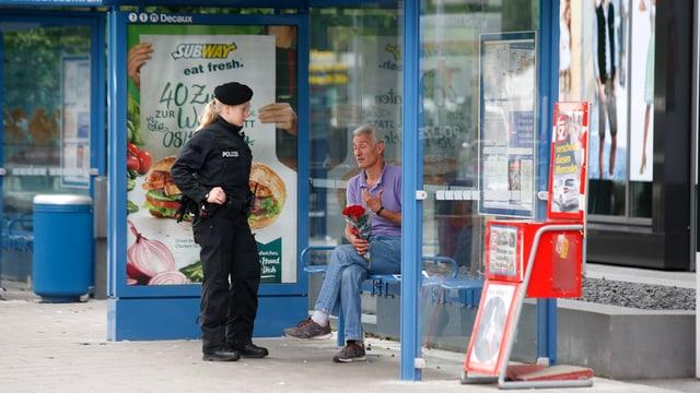 Mann mit Rosen in der Hand spricht mit einer Polizistin
