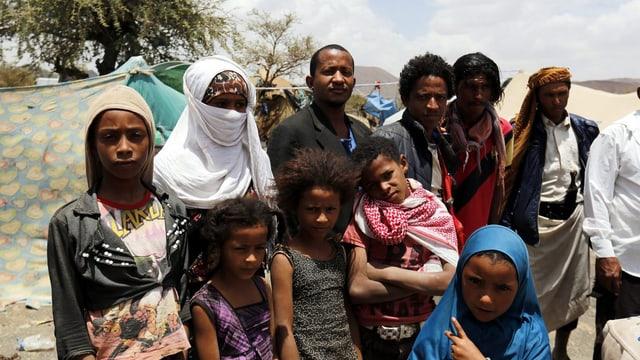 Eine Gruppe Frauen, Kinder und Männer vor Zelten in einem Flüchtlingslager.