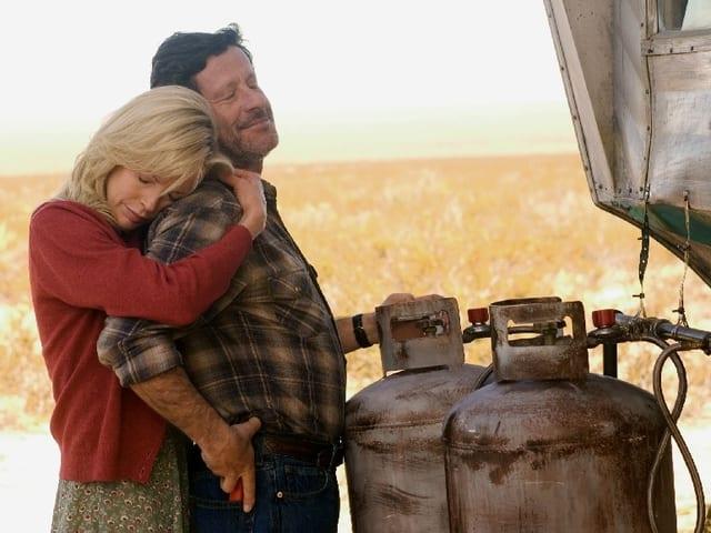 Gina schmiegt sich an den Rücken von Nick, der vor zwei Gasflaschen steht.