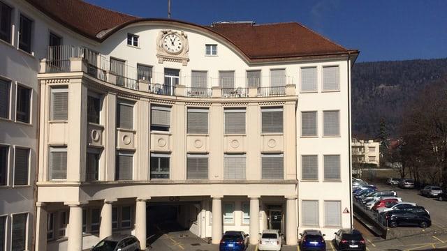 Steinernes Fabrikgebäude mit Säulen und Uhr.