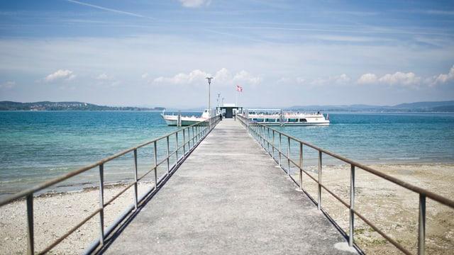 Landesteg und ein Schiff das anlegt, dahinter der Untersee und ein blauer Himmel mit Wolken
