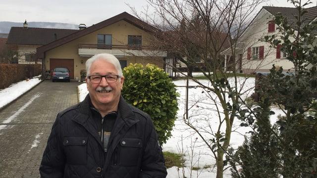 Mann vor Einfamilienhaus