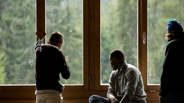 Männer vor Fenster.