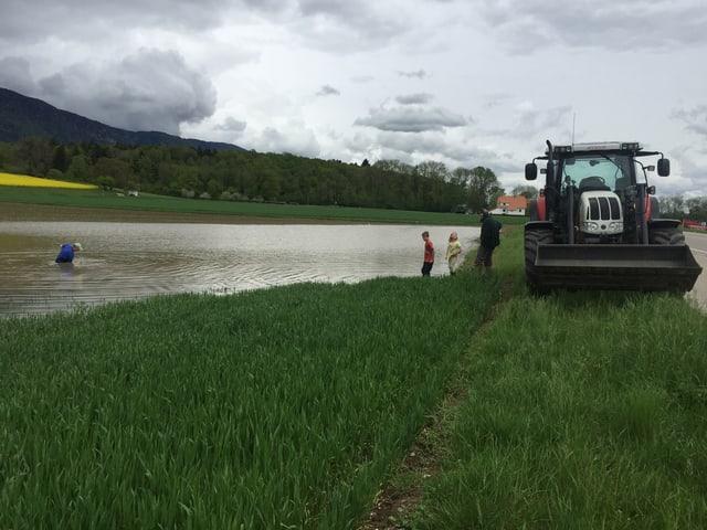 Ein Bauer steht in einer riesigen Wasserlache auf seinem Acker. Daneben steht auf der Strasse ein Traktor.