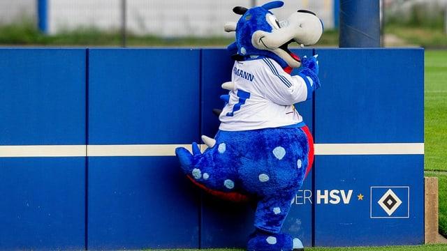 HSV-Maskottchen Dino Hermann steht an einer blauen Wand.