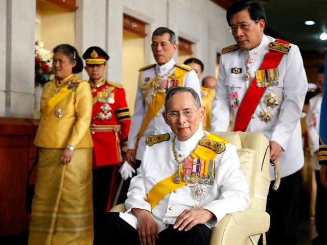 König Bhumibol sitzt in einem Rollstuhl.