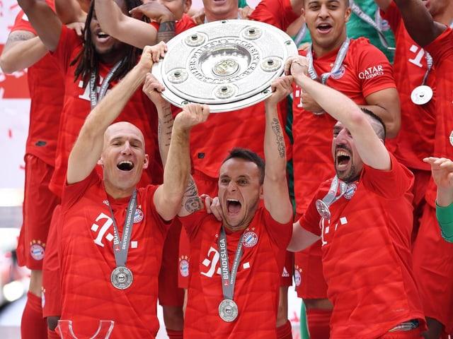 Die scheidenden Arjen Robben, Rafinha und Franck Ribéry stemmen gemeinsam die Meisterschale.