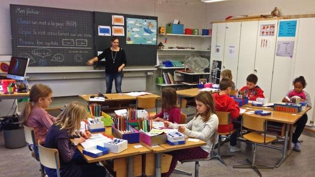 Kinder und eine Lehrerin in einem Klassenzimmer