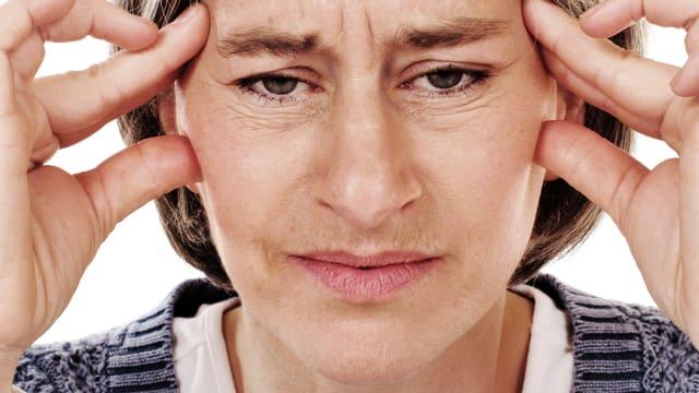 Frau mittleren Alters hält sich die Schläfen und schaut schmerzerfüllt in die Kamera.
