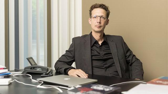 Politologe Michael Hermann sitzt an seinem Pult.