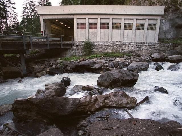 Zu sehen ist ein Wildbach und eine betonierte Brücke. Am anderen Ende der Brücke ist der Eingang zu einem Betonklotz.