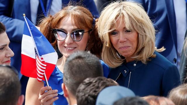 Macron mit einer Frau aus dem Volk und mit Frankreich-Fähnchen.