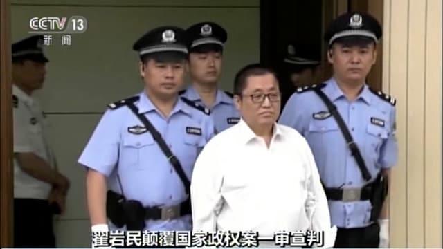 Zhai Yanmin, hinter ihm drei Polizisten.
