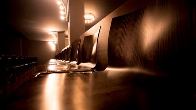 Stuhlreihe in einem leeren Theater in festlichem Licht.