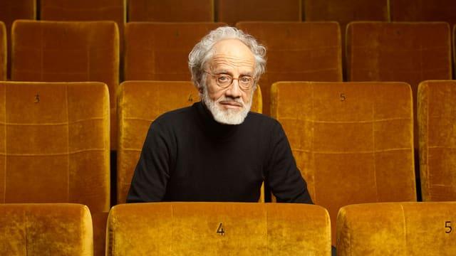 Markus Imhoof in einem Kinosaal mit goldenen Sesseln.