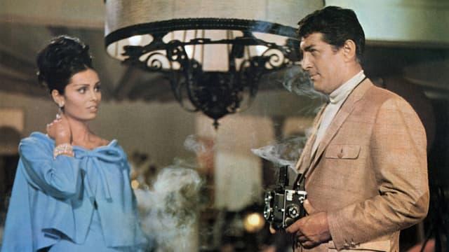 Ein Mann mit rauchendem Fotoapparat und eine Frau schauen sich gegenseitig an.
