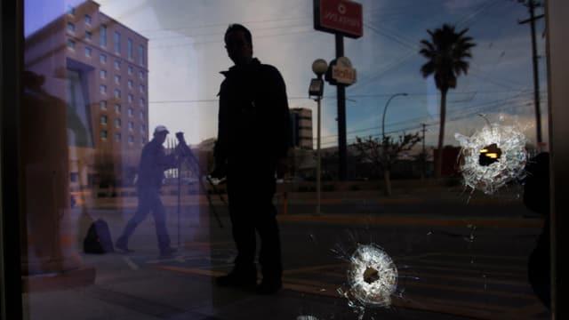 Journalisten stehen vor einem Fenster mit Einschusslöchern.