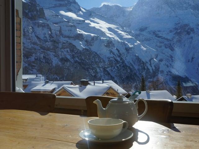 Ein Teekrug steht vor einem Fenster mit schöner Bergsicht.