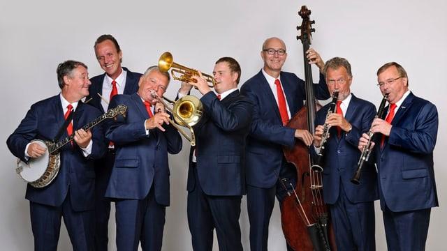 Die sieben Musiker in blauen Anzügen und mit ihren Instrumenten auf einem Gruppenfoto.