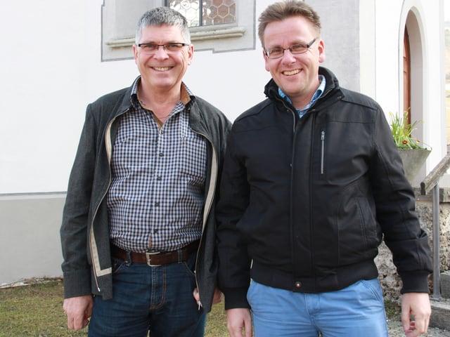 Die beiden Männer tragen Hemden und dünne Westen und stehen vor dem Eingang der Kirche.