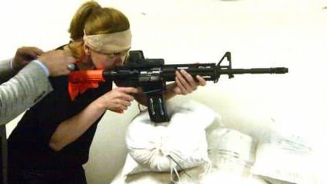 Eine Frau stützt ein Sturmgewehr auf Sandsäcken ab.