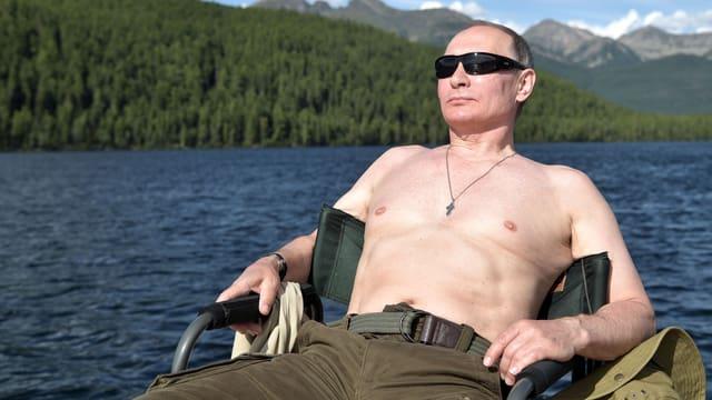 Putin sonnt sich auf einem Stuhl, hinter ihm ein Bergsee. (5. August 2017)