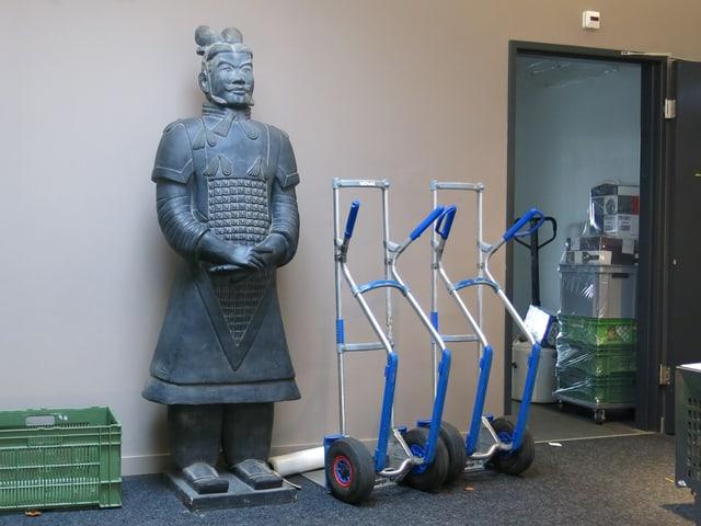 Grosse Krieger-Statue neben Lasten-Rolli