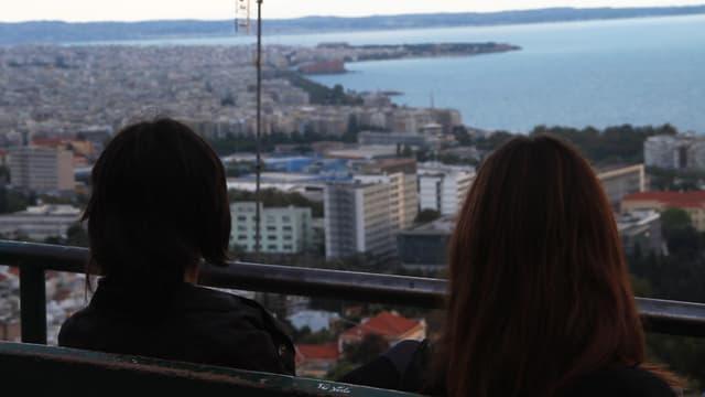Zwei Frauen von hinten, sie blicken auf eine Stadt am Meer.