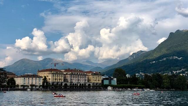 Blick über den Luganersee zur Stadt Lugano, dahinter grosse Quellwolken.