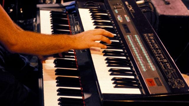 Eine Hand greift in die Tasten eines Synthesizers mit dem Label DX7.
