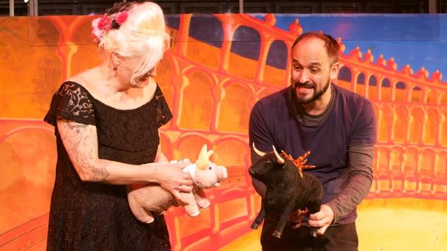Frau mit Stoffschwein und Mann mit Stoffstier in der Hand