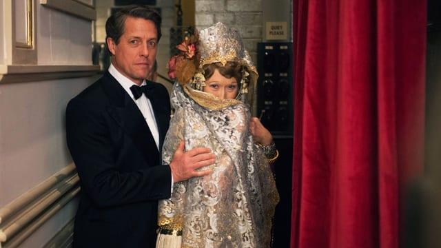 Meryl Streep im extravaganten Kostüm als Florence Foster und Hugh Grant im Anzug als ihr Ehemann.
