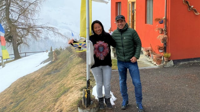 Silvio e Dawa Capaul avant lur chasa cun la bandiera dal tibet