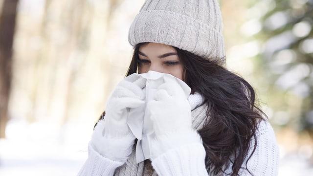 Symbolbild: Junge Frau schnäuzt sich die Nase.