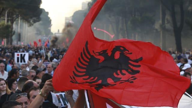 Leute mit albanischer Flagge am demonstrieren.