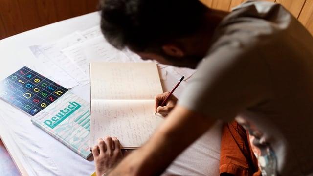 Asylsuchender lernt Deutsch und schreibt in ein Heft.