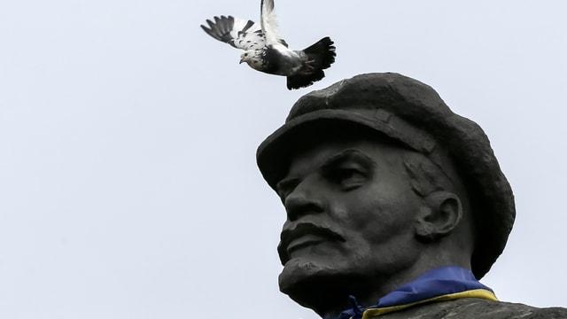 Kopf von Lenin-Statue, Taube fliegt daran vorbei.