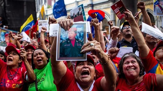 Unzählige freudige Venezolaner strecken Bilder mit Maduro und Chávez in die Kamera und schreien.