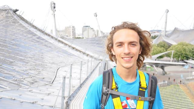 Ein Mann steht vor dem Olympiadach.