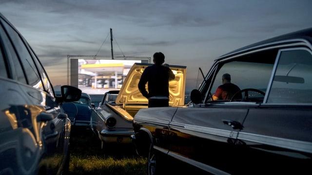 Ein Autokino, viele Oldtimer-Autos, ein Mann öffnet die Heckklappe seines Kofferraums.